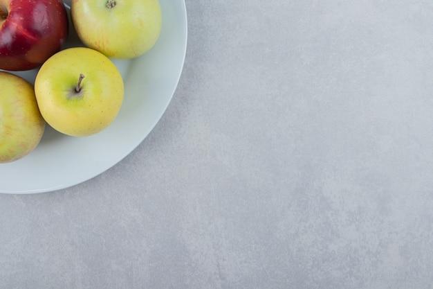 Букет из свежих яблок на белой тарелке