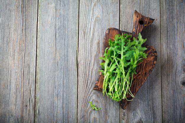 Букет свежей рукколы на деревянной доске на старой деревянной поверхности