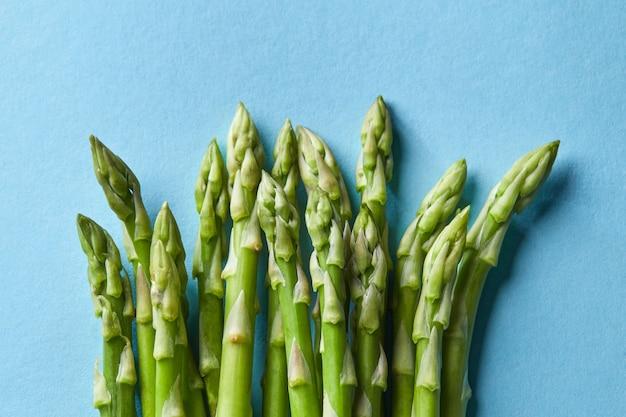 블루에 고립 된 신선한 아스파라거스의 무리입니다. 개념 건강 채식 음식입니다. 플랫 레이