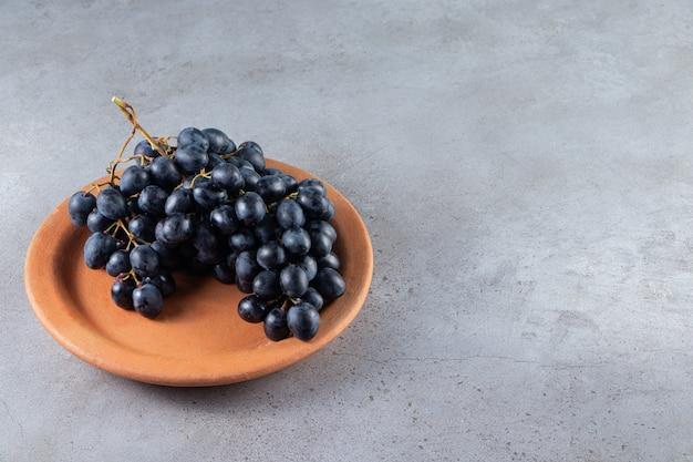 石のテーブルの上の粘土板の新鮮な黒ブドウの束。