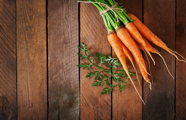 Букет из свежей моркови с зелеными листьями над деревянным столом