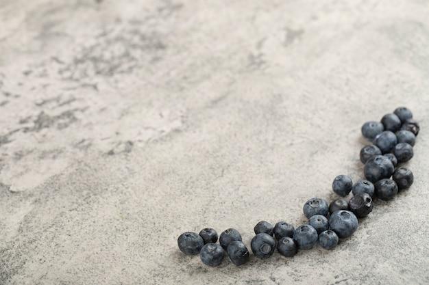 石の背景に配置された新鮮なおいしいブルーベリーの束。