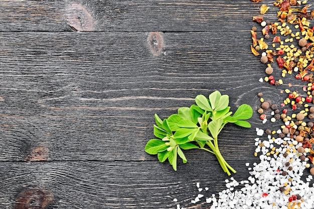 緑の葉と白い花、塩、コショウ、黒い木の板の背景にフェヌグリーク種子と新鮮なフェヌグリークの束