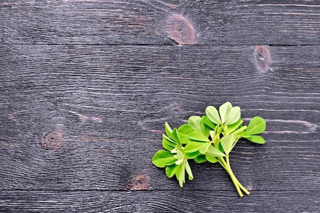 黒い木の板の背景に白い花と緑の葉を持つ新鮮なフェヌグリークの束