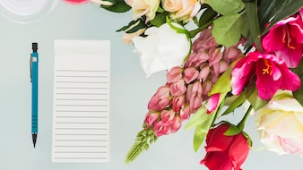 Bunch of fresh flowers with pen and notepad on desk