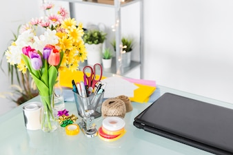 Bunch of fresh flowers with stationeries on desk