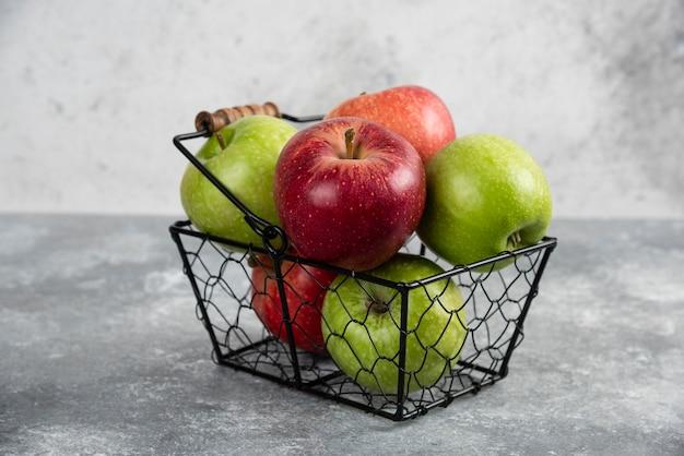 금속 바구니에 넣은 신선한 녹색 및 빨강 사과 한 뭉치.