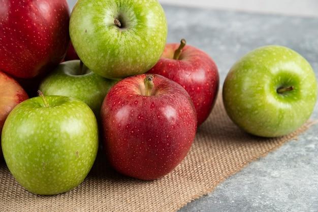Связка свежих зеленых и красных яблок на мешковине.