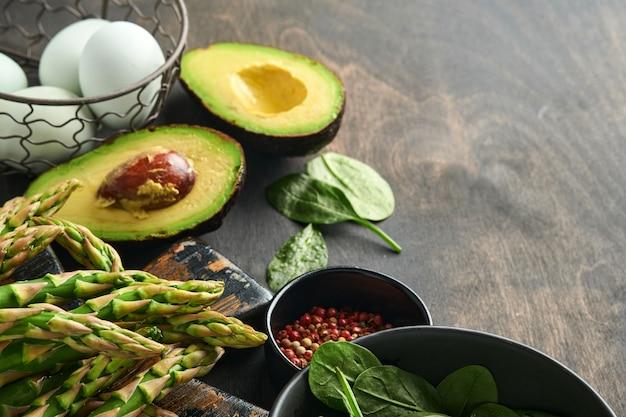 검은색 오래된 나무 배경에 신선한 녹색 유기농 아스파라거스 시금치, 아보카도, 닭고기 달걀, 후추 조미료 뭉치, 위쪽 전망. 복사 공간이 있는 음식 요리 배경. 조롱.