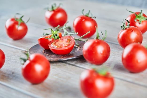 木製のテーブルの上に新鮮なジューシーなトマトとトマトのスライスの束。