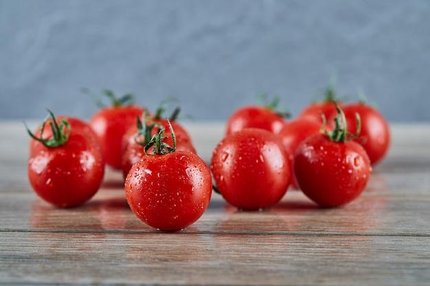 木製のテーブルに新鮮なジューシーなトマトの束。
