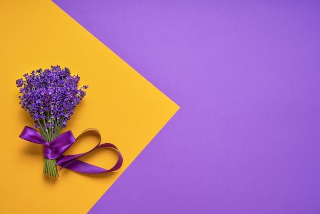 노란색-보라색 배경에 신선한 라벤더의 무리. 보라색 꽃. 장소 인사말 꽃 카드
