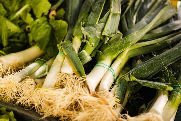 Куча свежих овощей лука-порея в ящике на рынке