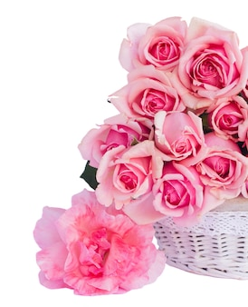 バスケットの新鮮なピンクの咲くバラの束は、白い背景で隔離のクローズアップ