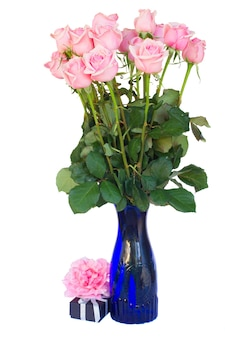 白い背景で隔離の青い花瓶の新鮮なピンクのバラの束