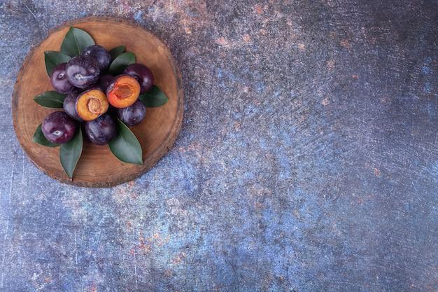 Букет из свежих фиолетовых слив на деревянной доске.