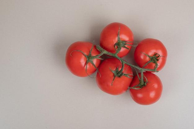흰색 테이블에 녹색 줄기와 신선한, 빨간 토마토의 무리.