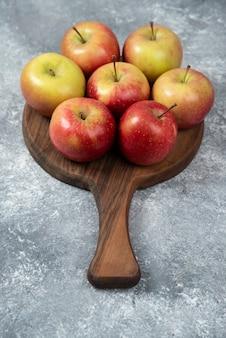 木の板の上に置かれた新鮮な熟したリンゴの束。