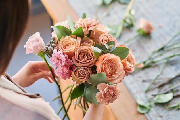 Букет из свежих роз и гвоздик пастельных тонов в руках молодого флориста, составляющего букеты на рабочем месте