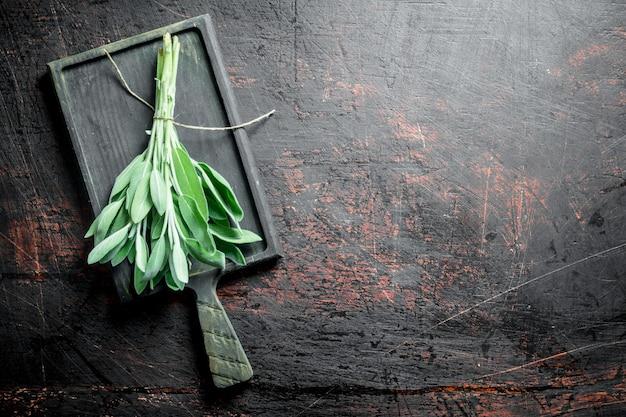 まな板の上の新鮮なサルビアの束。暗い素朴な背景に