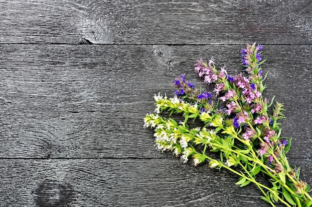 黒い木の板の背景に花と新鮮なおいしいの束