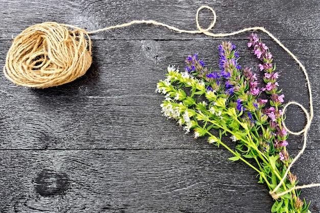 緑の葉と花、黒い木の板に対するより糸のコイルと新鮮なおいしいの束