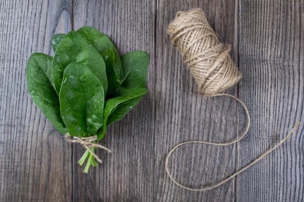 Пук свежего шпината с корнями на деревенском деревянном столе. эко продукты