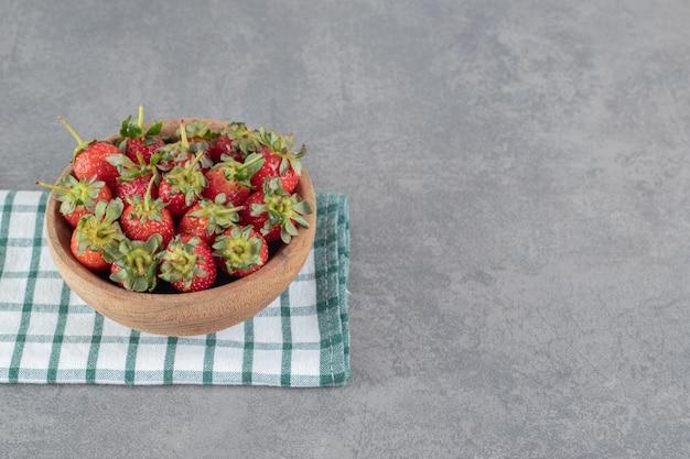 木製のボウルに新鮮なイチゴの束。高品質の写真