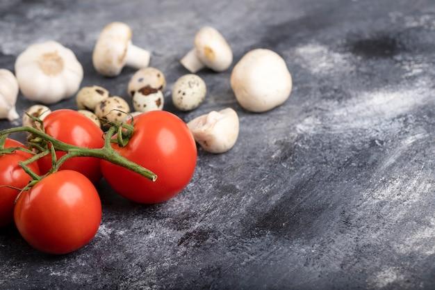 Букет из свежих овощей с сырыми перепелиными яйцами на мраморе.