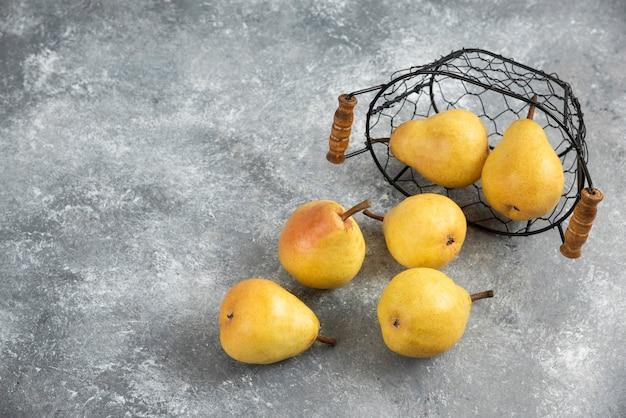 大理石の表面の金属製のバケツに新鮮な黄色の梨の束。