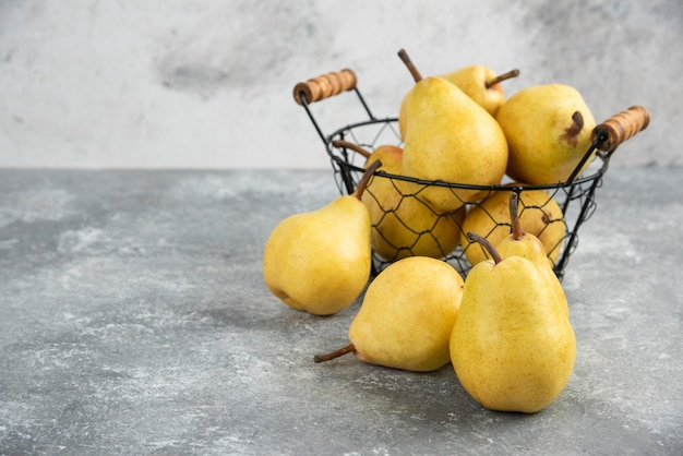 Букет из свежих желтых груш в металлическом ведре на мраморной поверхности.