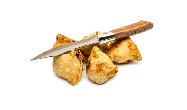 격리된 흰색 배경에 날카로운 칼로 튀긴 수제 사모사 무리