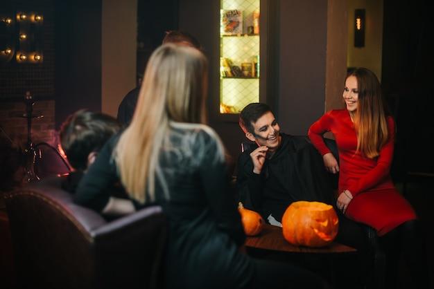 暗くて居心地の良いカフェでハロウィーンを楽しんでいる2人の男と2人の女の子からのたくさんの友達。テーブルに刻まれたカボチャ。若い人たちのカラフルなメイク。