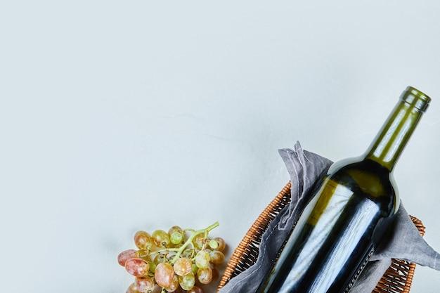 포도의 무리와 회색 배경에 와인 한 병. 고품질 사진