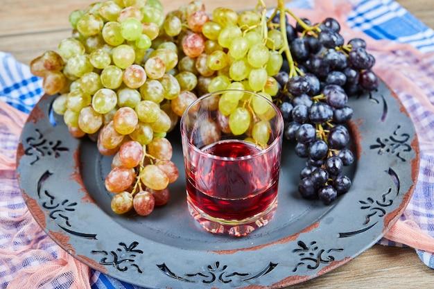 Гроздь винограда и стакан сока на керамической тарелке со скатертями.