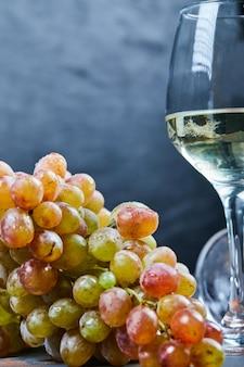 青の背景にブドウの房と白ワインのグラス。高品質の写真
