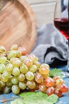 포도의 무리와 파란색 배경에 와인 한 잔. 고품질 사진