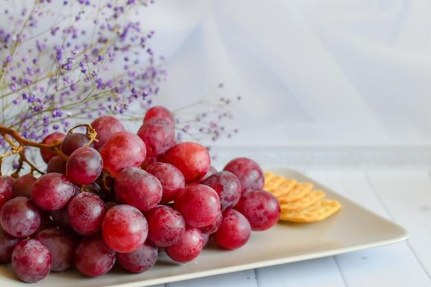 葡萄とクラッカーの束を皿に。ワインのおやつと静物。明るい背景のベージュの大皿に赤ブドウ。