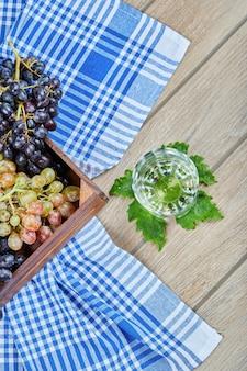 나무 바구니에 포도의 무리와 나무 테이블에 와인 한 잔. 고품질 사진