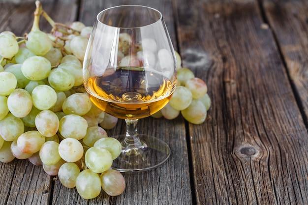 Гроздь винограда на деревянный стол с бокалом коньяка