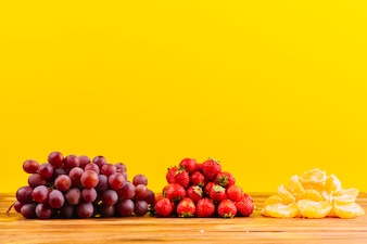 Bunch of grapes; strawberries and slice of orange on wooden table against yellow background