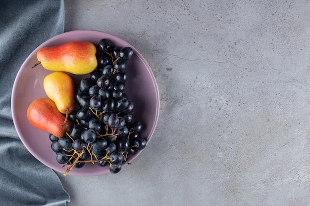 石のテーブルの上の紫色のプレートに赤黄色の梨とブドウの束。