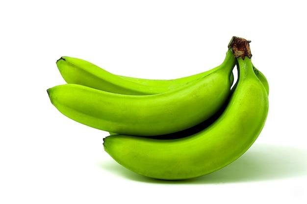 Букет из зеленых бананов, на белом столе, копией пространства, по горизонтали.