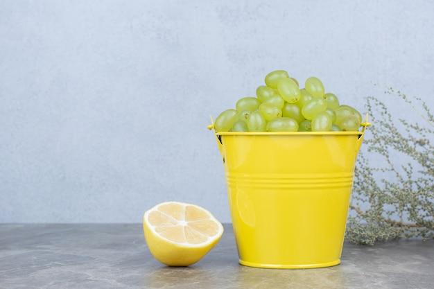 ハーフカットレモンとバケツの緑のブドウの束。