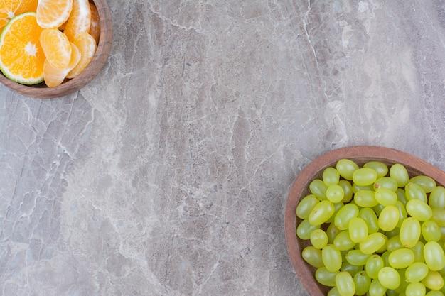 木製のボウルと柑橘系の果物の緑のブドウの束。