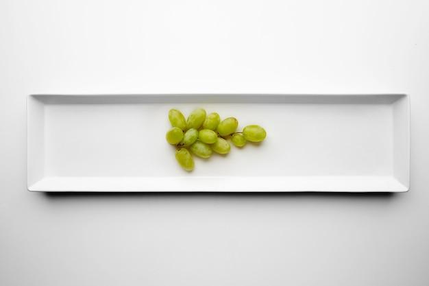 白いプレートの中央に分離された緑のマスカットブドウの束
