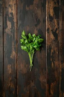 Пук зеленой петрушки на деревянном деревенском столе. вид сверху.