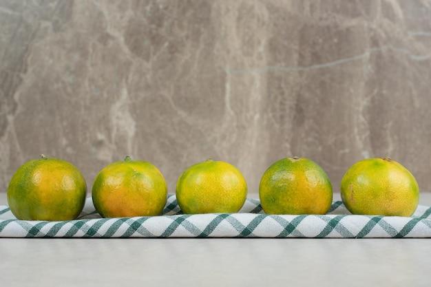 縞模様のテーブルクロスに緑のみかんの束