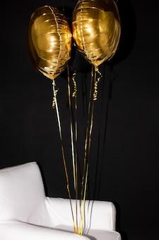생일 파티 또는 기타 축하 행사의 장식으로 흰색 가죽 안락 의자에 묶인 부풀린 황금색 풍선 무리