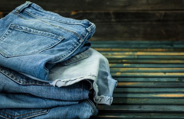木製の壁にジーンズの束、ファッショナブルな服